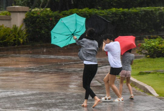 In this file photo, tourists try to contend with failing umbrellas in Tumon during rain and winds gusts brought on by Typhoon Wutip.