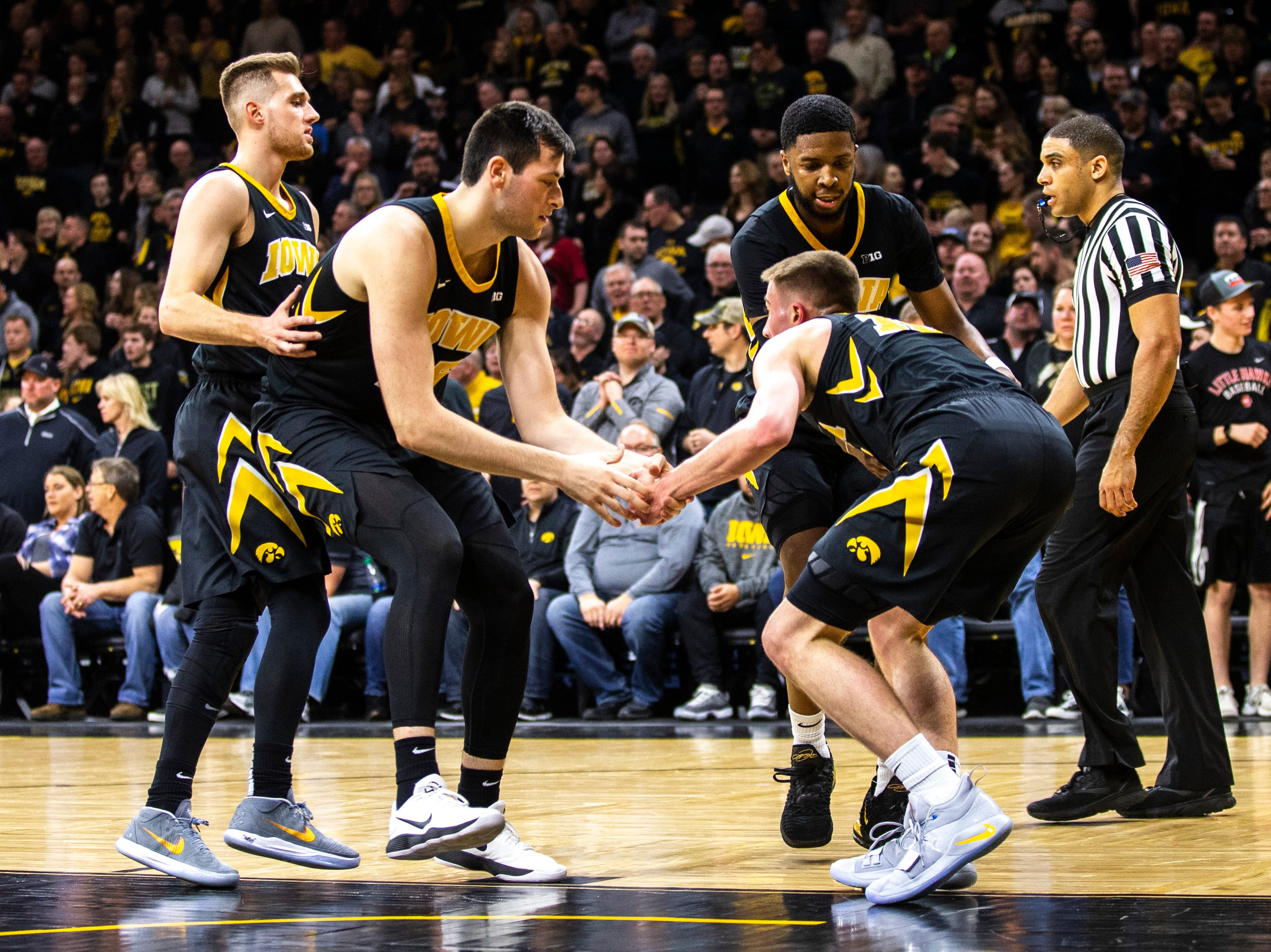 Iowa guard Joe Wieskamp (10) gets helped up by Iowa forward Ryan Kriener (15) and Iowa guard Isaiah Moss (4) during a NCAA Big Ten Conference men's basketball game on Friday, Feb. 22, 2019 at Carver-Hawkeye Arena in Iowa City, Iowa.