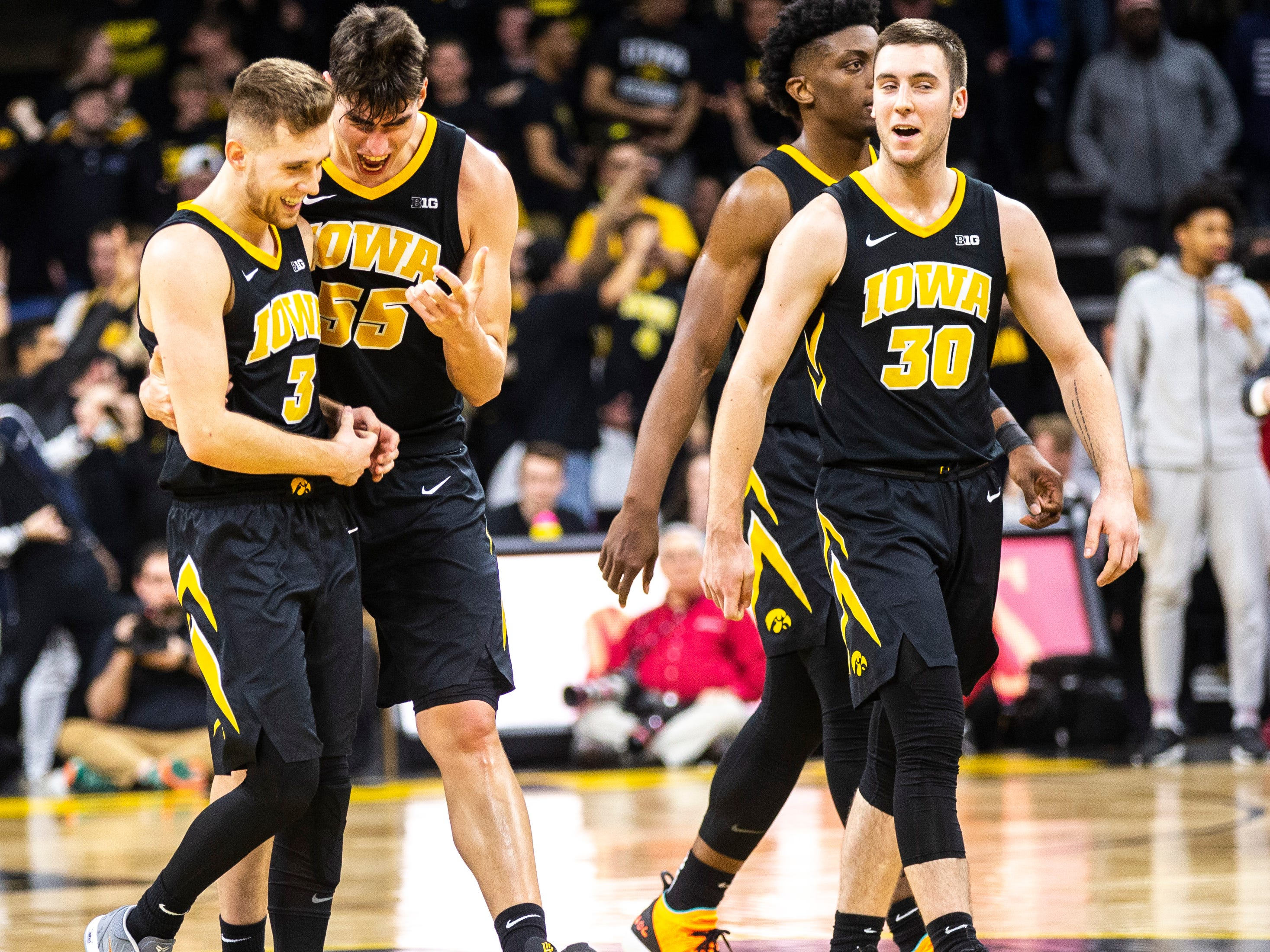 Iowa guard Jordan Bohannon (3) is embraced by Luka Garza (55) while Connor McCaffery (30) and Tyler Cook, second from right, celebrate during a NCAA Big Ten Conference men's basketball game on Friday, Feb. 22, 2019 at Carver-Hawkeye Arena in Iowa City, Iowa.