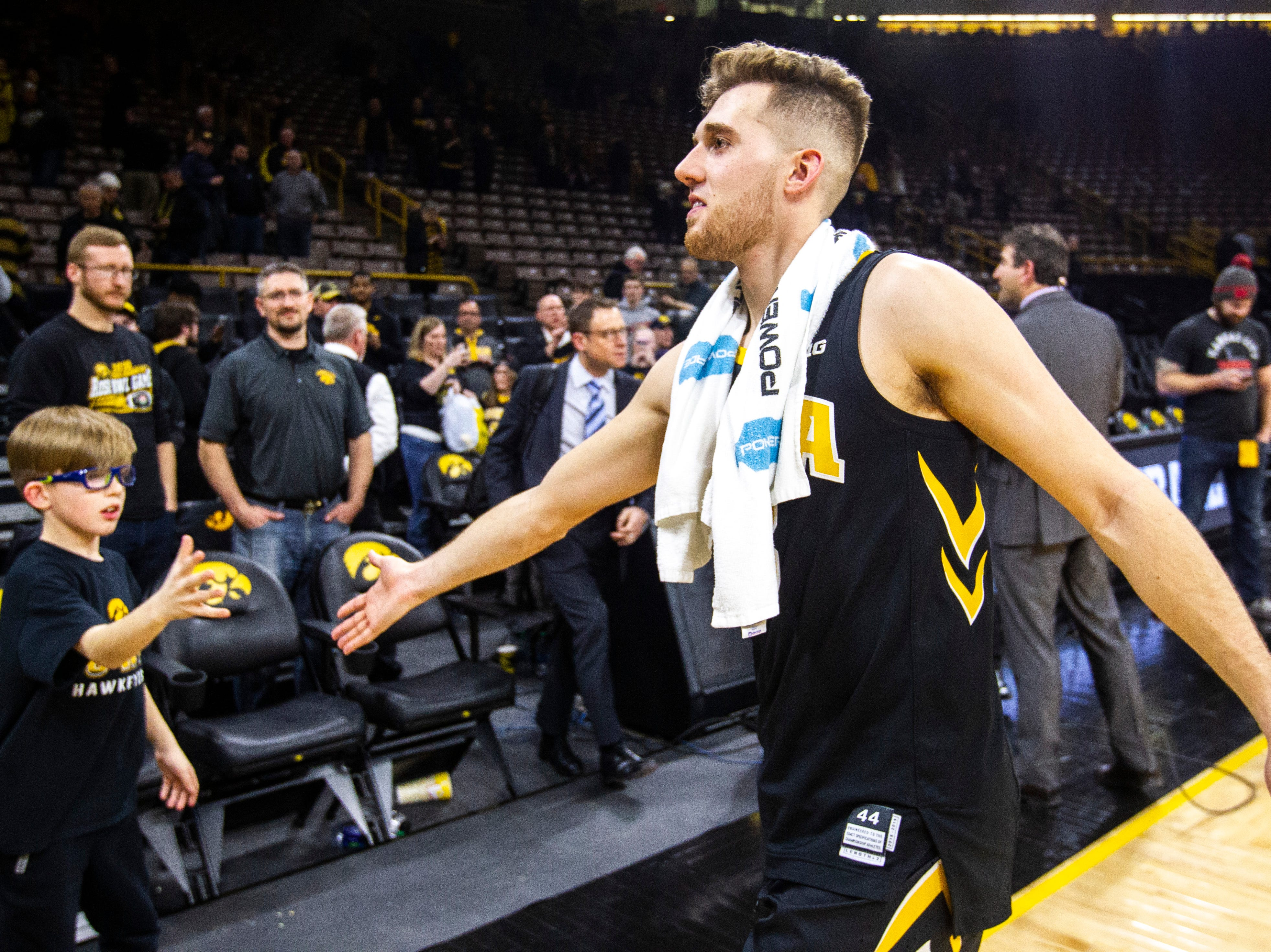 Iowa guard Jordan Bohannon (3) high-fives a fan after a NCAA Big Ten Conference men's basketball game on Friday, Feb. 22, 2019 at Carver-Hawkeye Arena in Iowa City, Iowa.