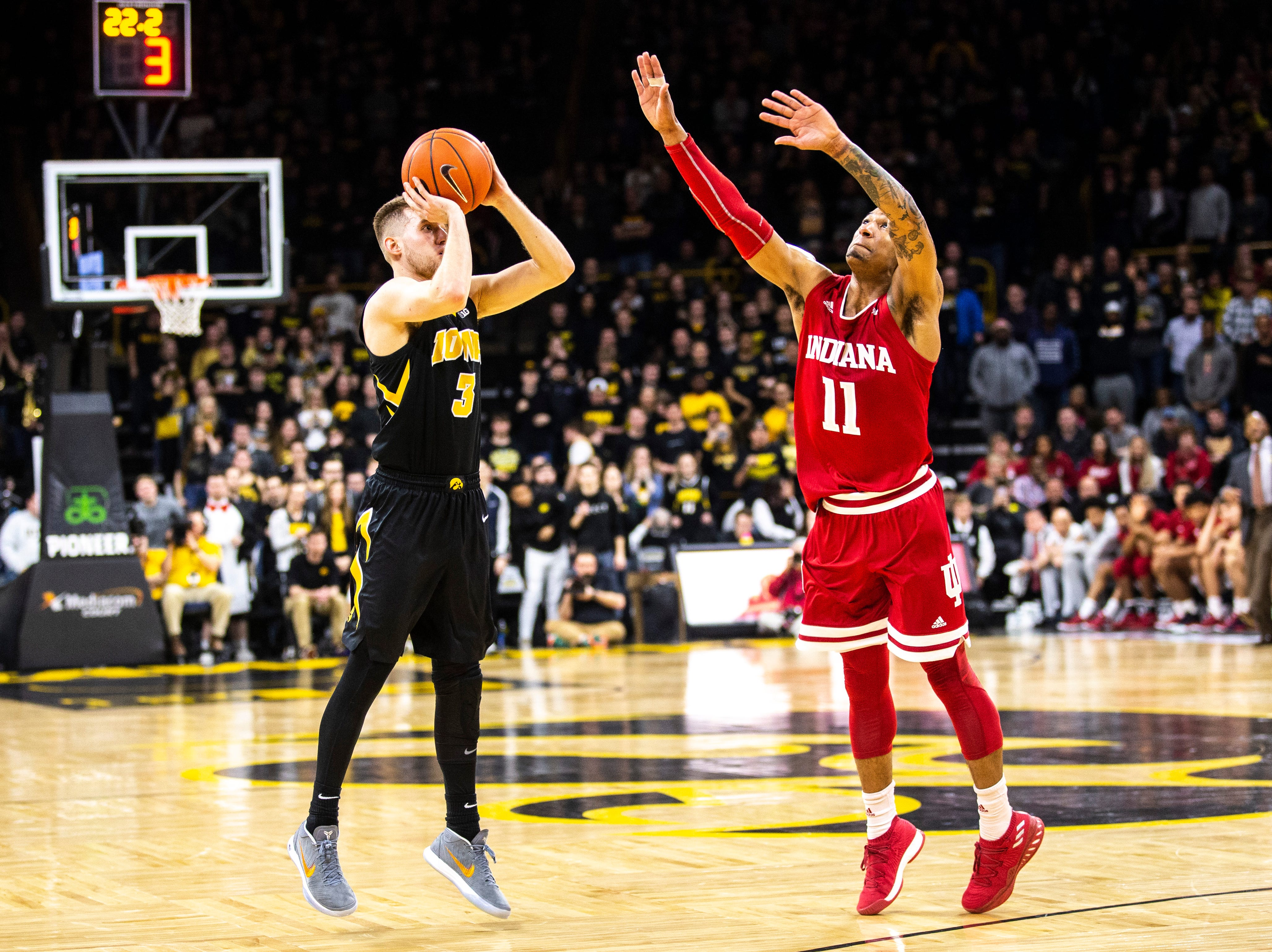 Iowa guard Jordan Bohannon (3) shoots 3-point basket in overtime during a NCAA Big Ten Conference men's basketball game on Friday, Feb. 22, 2019 at Carver-Hawkeye Arena in Iowa City, Iowa.