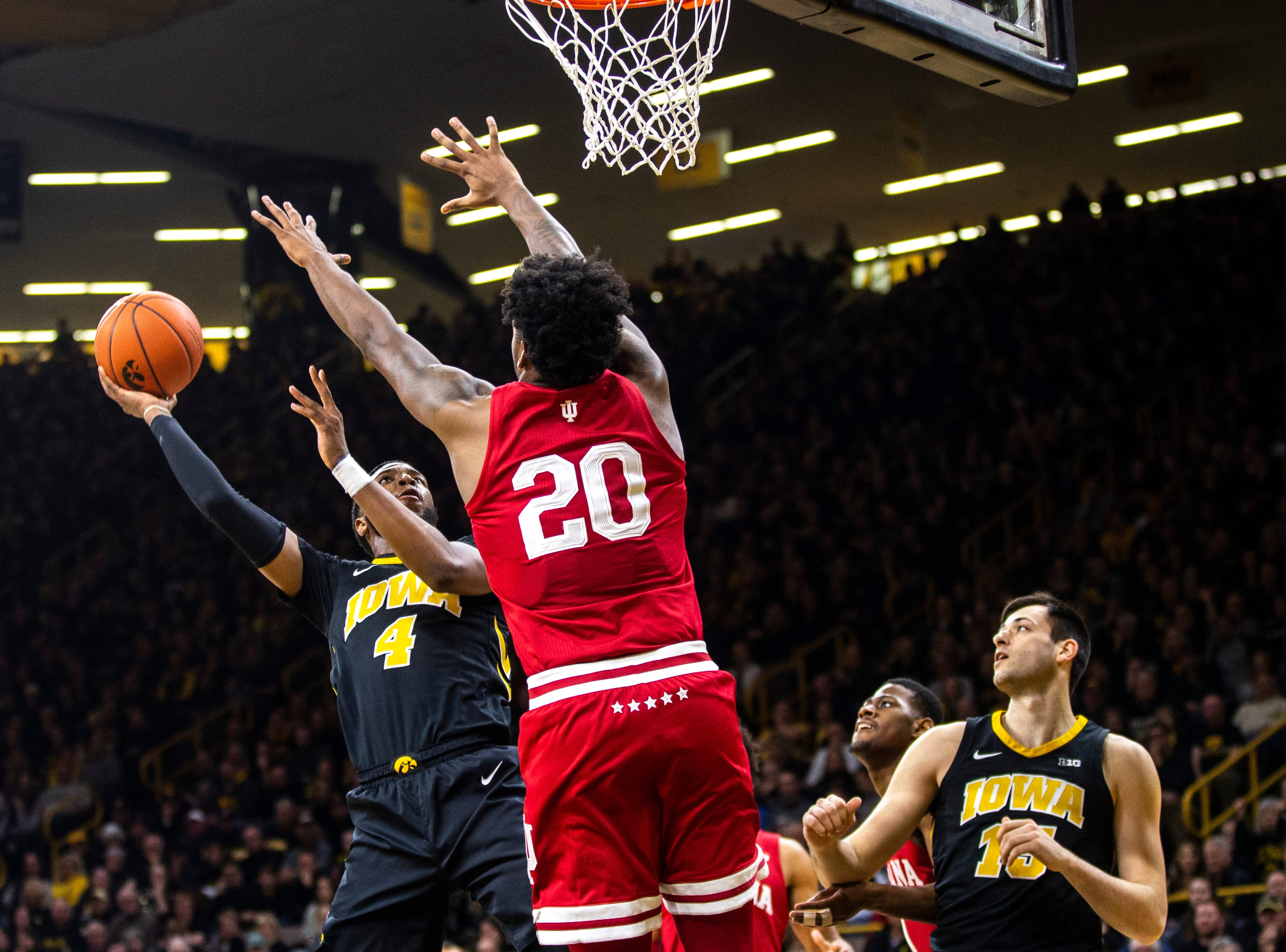 Iowa guard Isaiah Moss (4) attempts a basket while Indiana forward De'Ron Davis (20) defends during a NCAA Big Ten Conference men's basketball game on Friday, Feb. 22, 2019 at Carver-Hawkeye Arena in Iowa City, Iowa.