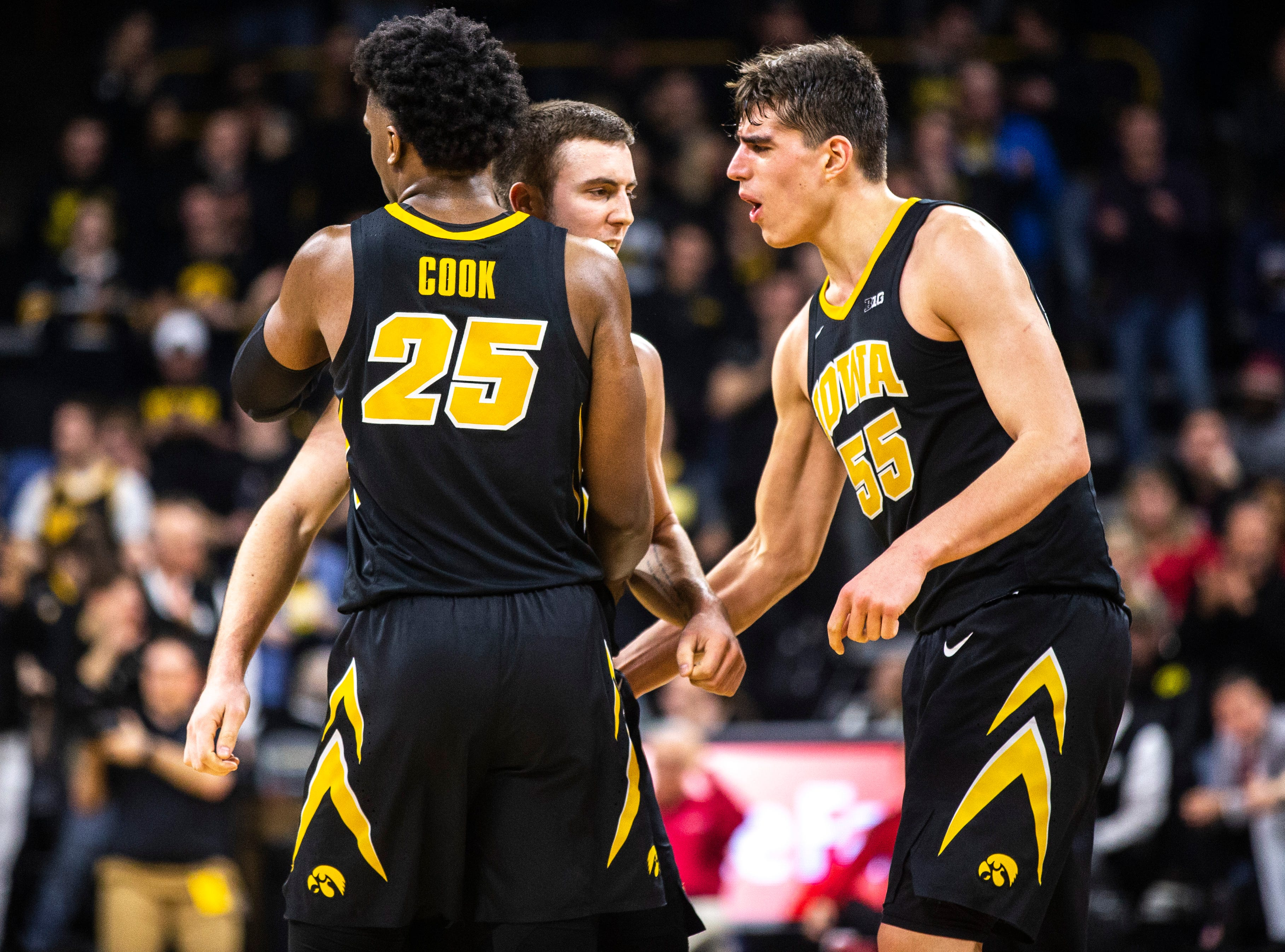 Iowa guard Connor McCaffery is embraced by Iowa forward Tyler Cook, left, and Luka Garza (55) after getting fouled during a NCAA Big Ten Conference men's basketball game on Friday, Feb. 22, 2019 at Carver-Hawkeye Arena in Iowa City, Iowa.