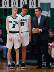 Monrovia Bulldogs head coach Kyle Swafford talks with Jaylen Sprague (31) and Joe Williams (3) in the first half of their game at Monrovia High School on Friday, Feb 22., 2018.