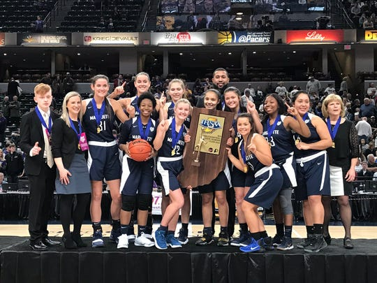 Class A champions Marquette Catholic celebrate a second-straight girls basketball state title at Bankers Life Fieldhouse on Saturday.