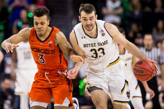 Notre Dame's John Mooney (33) drives downcourt next to Virginia Tech's Wabissa Bede (3) during the second half of an NCAA college basketball game Saturday, Feb. 23, 2019, in South Bend, Ind. Virginia Tech won 67-59. (AP Photo/Robert Franklin)
