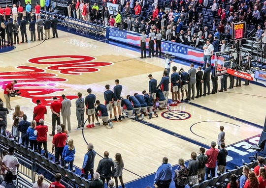 Six Ole Miss basketball players take a knee during the national anthem to protest a pro-Confederate rally that was being held on campus at the same time. The players knelt before their home game against Georgia on Saturday, Feb. 23, 2019. (Nathanael Gabler/The Oxford Eagle via AP)