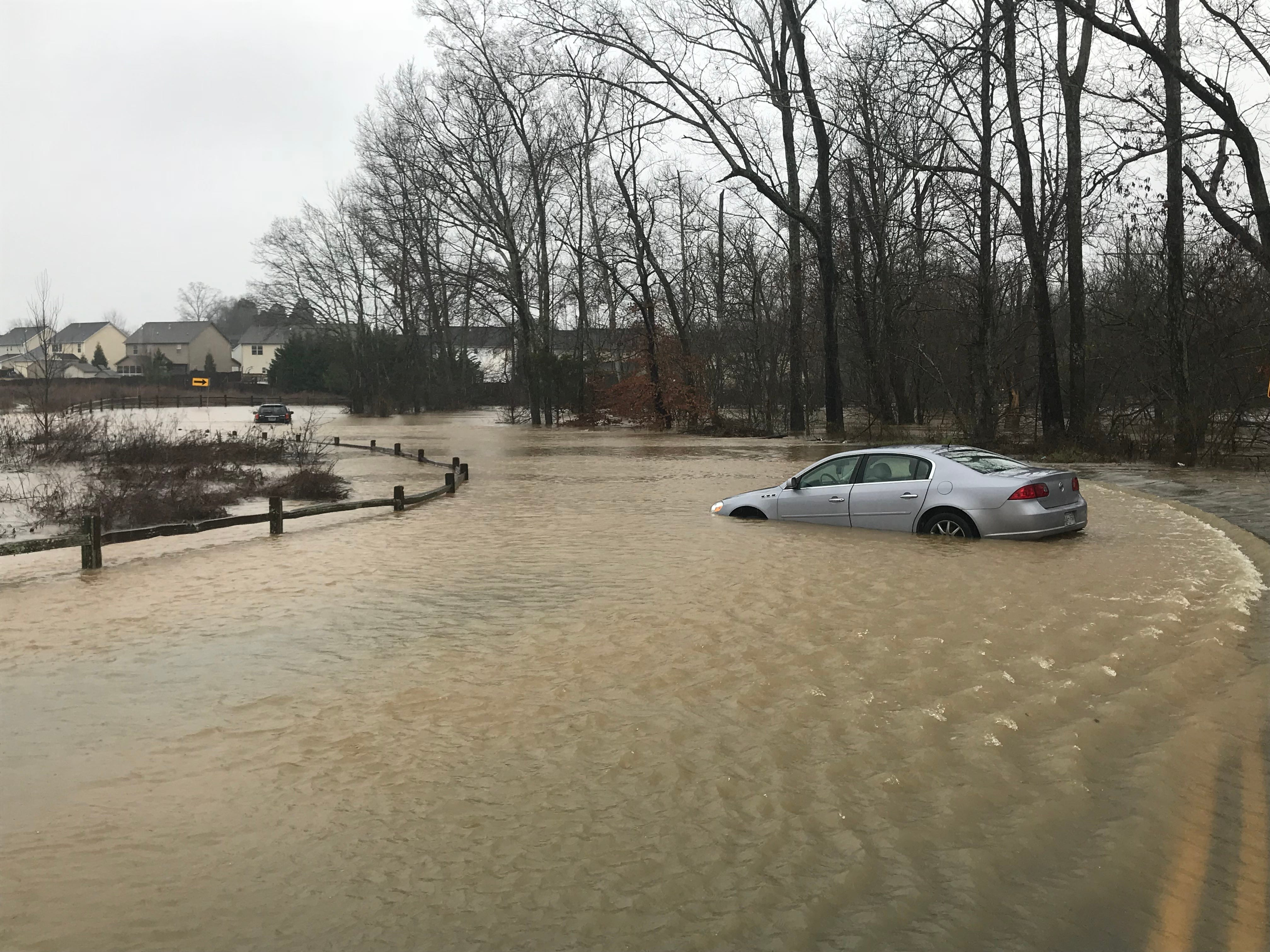 Brenda Colbert's Buick Lucerne (right) became trapped in floodwaters Saturday on Harrell Road in Knoxville. She was rescue by the Karns Fire Department on Feb. 23, 2019.