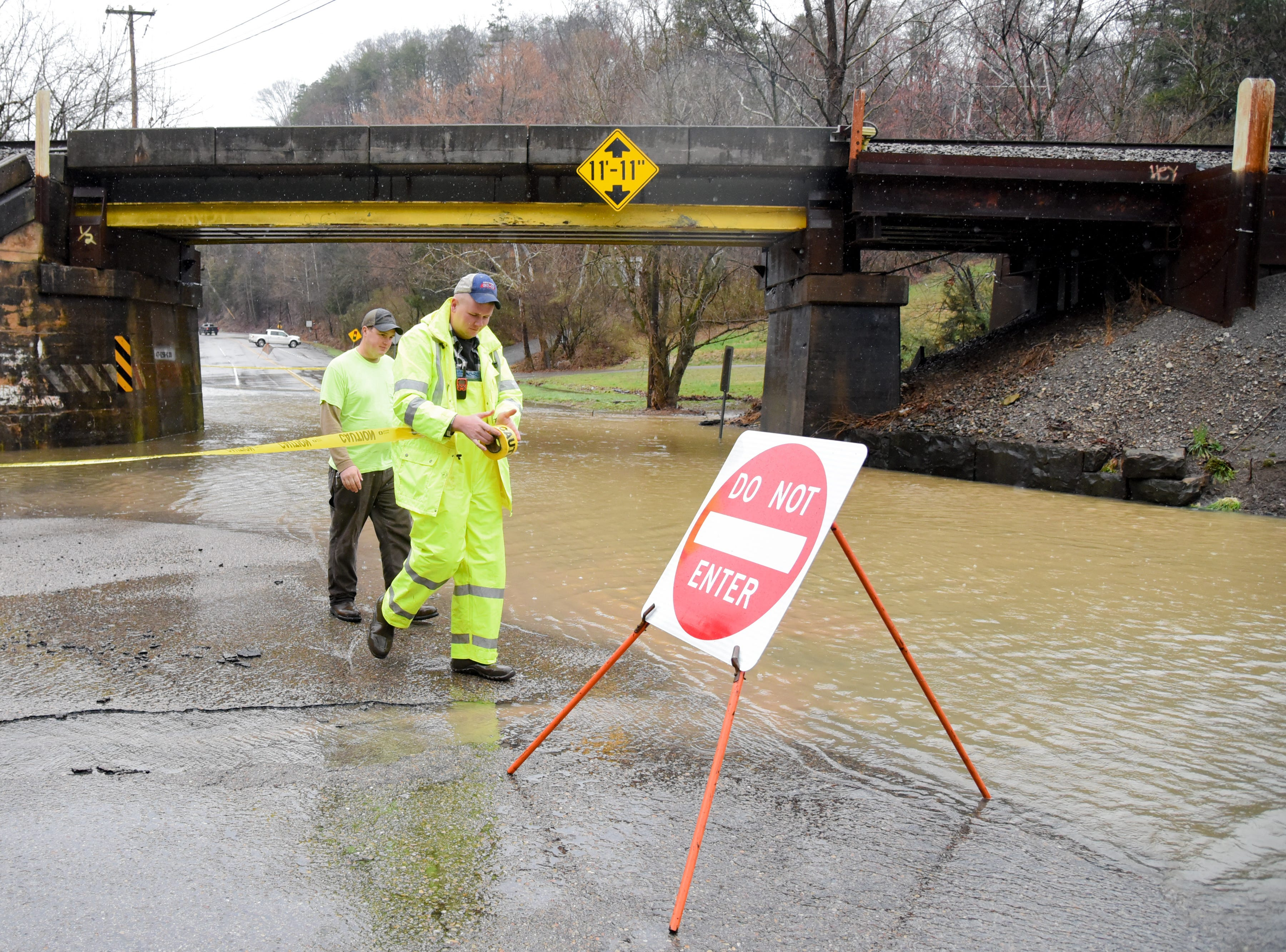 Knox County Highway Maintenance workers Chad Rutherford, left,  and Chad Ricker, right, close Central Avenue Pike at the intersection of Irwin Dr. due to floodwaters in Knox County Saturday Feb. 23, 2019. The Knoxville area could see between 2 and 3 inches of rain through the weekend.