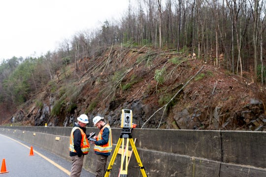 Workers take measurements and reading in a survey of the scene of a mudslide on I-40 eastbound in Clyde, North Carolina  near the Tennessee and North Carolina border on Saturday, February 23, 2019. Travel east and west on I-40 will be shut down for approximately four to seven days, with the east and west bound lanes to open with only one lane for around six weeks as crews continue repairs.
