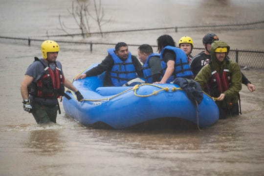 Three men are rescued by the Knoxville Fire Department from a stranded car off of 6th Street in Knoxville Saturday, Feb. 23, 2019. The Knoxville area could see between 2 and 3 inches through the weekend.
