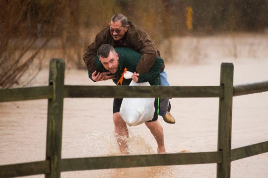 Matt Price gives neighbor Mike Altier a ride on his back through flood waters in Fountain City Saturday, Feb. 23, 2019.