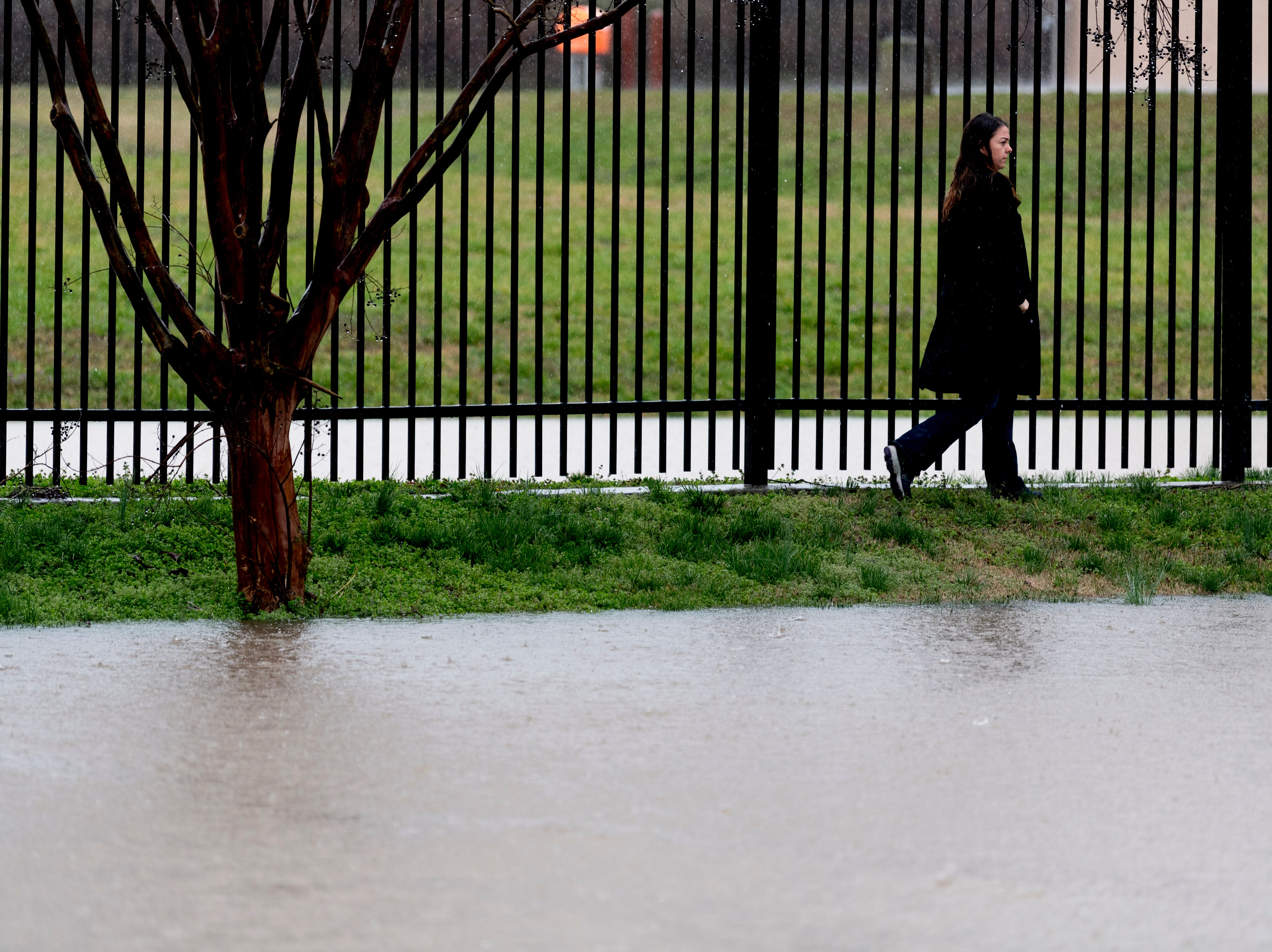A pedestrian walks along a flooded portion of North 6th Ave. during a heavy rainstorm in Knoxville, Tennessee on Saturday, February 23, 2019. The Knoxville area could see between 2 and 3 inches through the weekend.