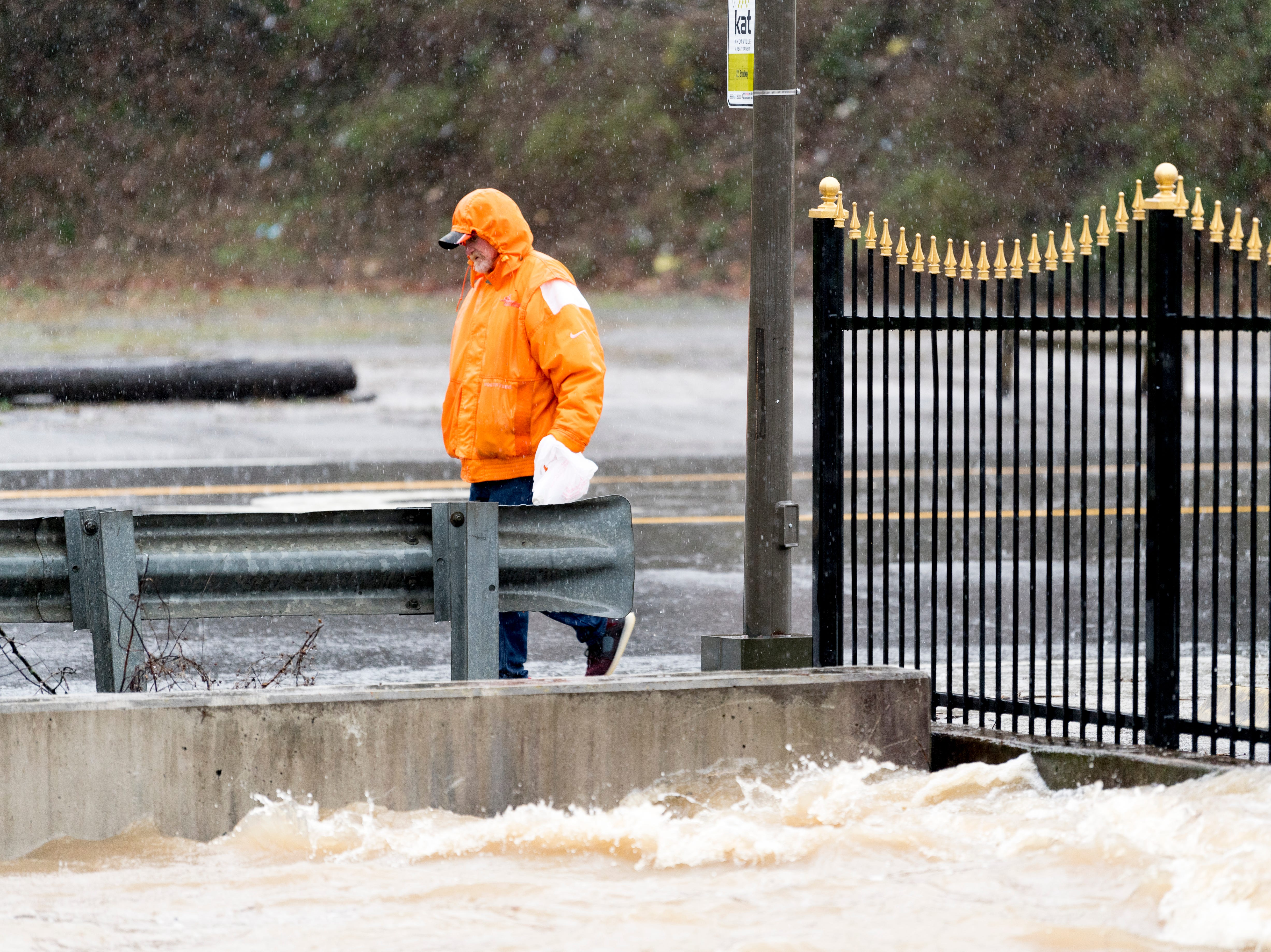 A pedestrian passes by an overflowing First Creek as seen from the Broadway Kroger during a heavy rainstorm in Knoxville, Tennessee on Saturday, February 23, 2019. The Knoxville area could see between 2 and 3 inches through the weekend.