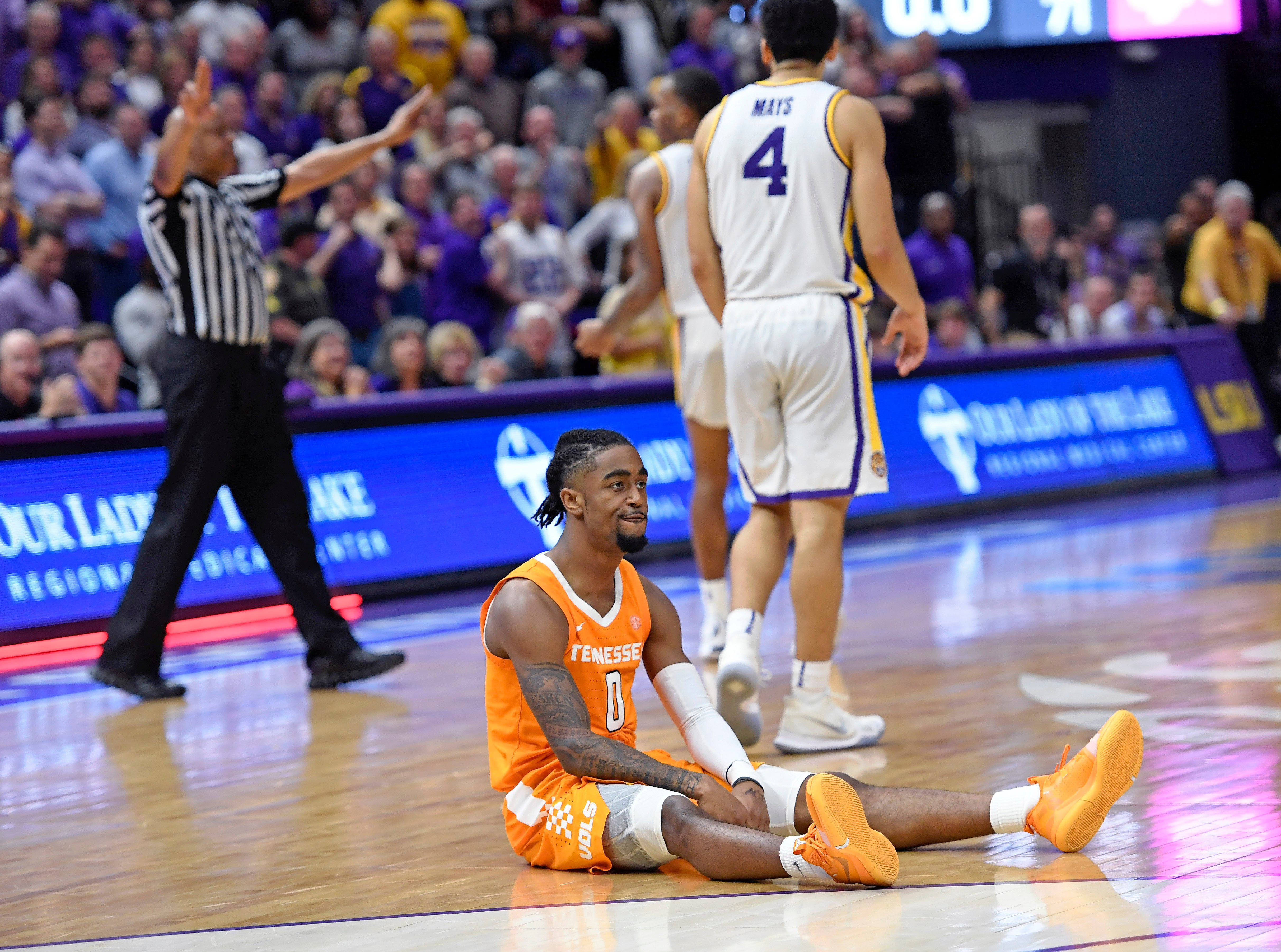 LSU guard Skylar Mays (4) walks away as Tennessee guard Jordan Bone (0) sits on the floor after slipping and unable to take a final shot in the second half of an NCAA college basketball game, Saturday, Feb. 23, 2019, in Baton Rouge, La. LSU won in overtime 82-80.(AP Photo/Bill Feig)