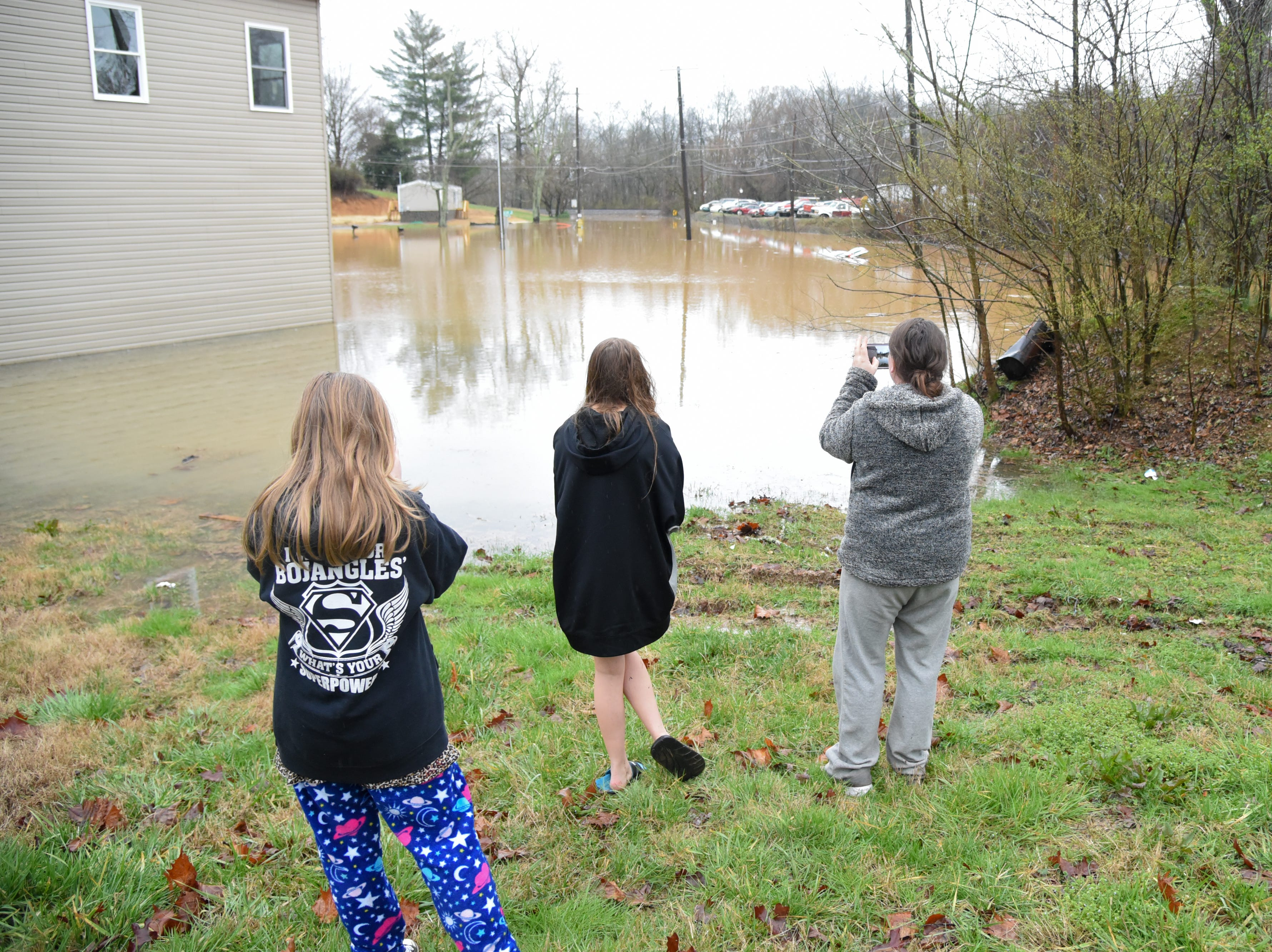Kristyn Lane and her daughters Rachel Lane and Kaitlyn Wells of Powell observe flooding in Powell Saturday Feb. 23, 2019. The Knoxville area could see between 2 and 3 inches of rain through the weekend.