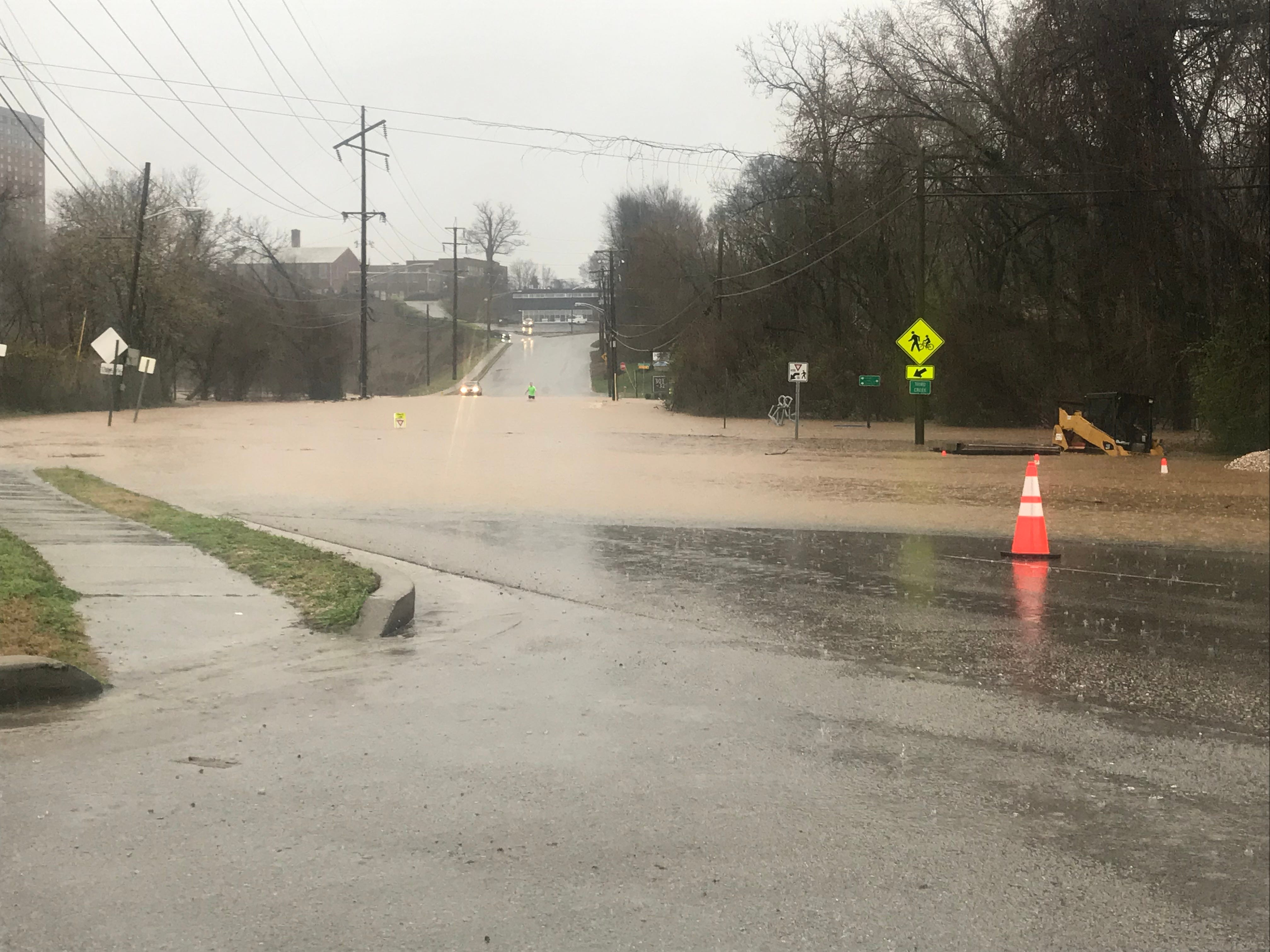 A pedestrian wades through the flooding water at Concord and Sutherland near University of Tennessee.