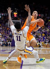 Tennessee forward Grant Williams (2) runs into LSU forward Kavell Bigby-Williams (11) over while driving the basket during overtime of an NCAA college basketball game, Saturday, Feb. 23, 2019, in Baton Rouge, La. Williams was called for charging. LSU won in overtime 82-80.(AP Photo/Bill Feig)