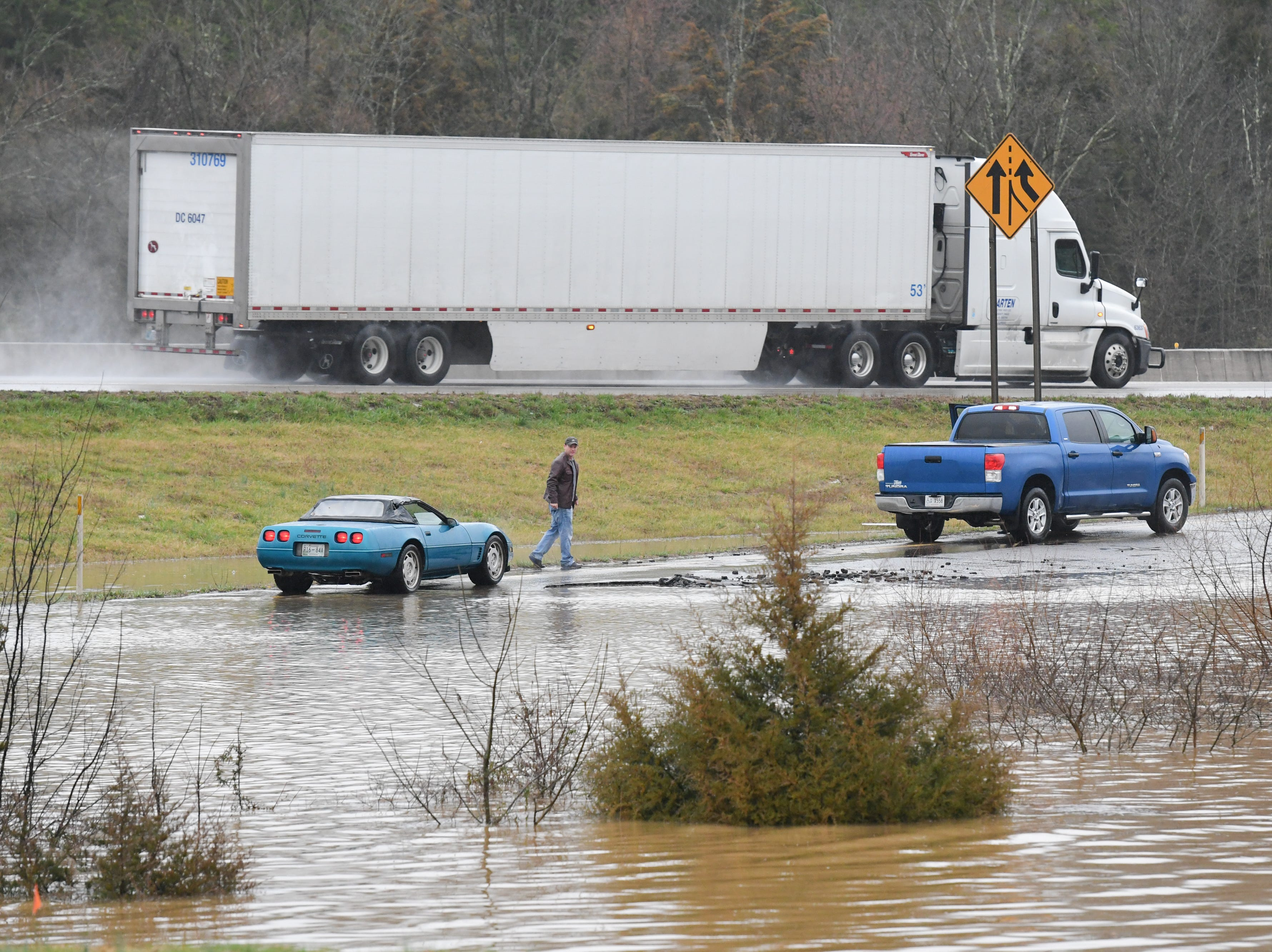 A motorist walks away after his car became disabled due to flooding on the entrance ramp to I-75 South from Emory Road in Knox County Saturday Feb. 23, 2019. The Knoxville area could see between 2 and 3 inches of rain through the weekend.