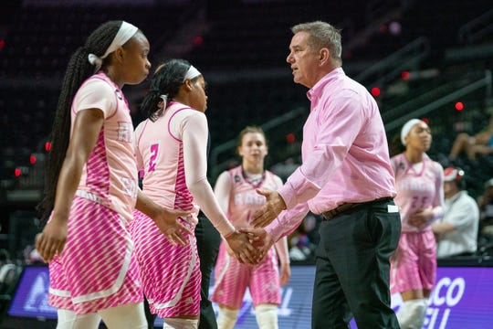 """UL women's basketball coach Garry Brodhead greets Ragin' Cajun players during last season's cancer research awareness """"Pink Game"""" against Texas State. This year's """"Pink Game"""" is Saturday vs. Georgia Southern."""