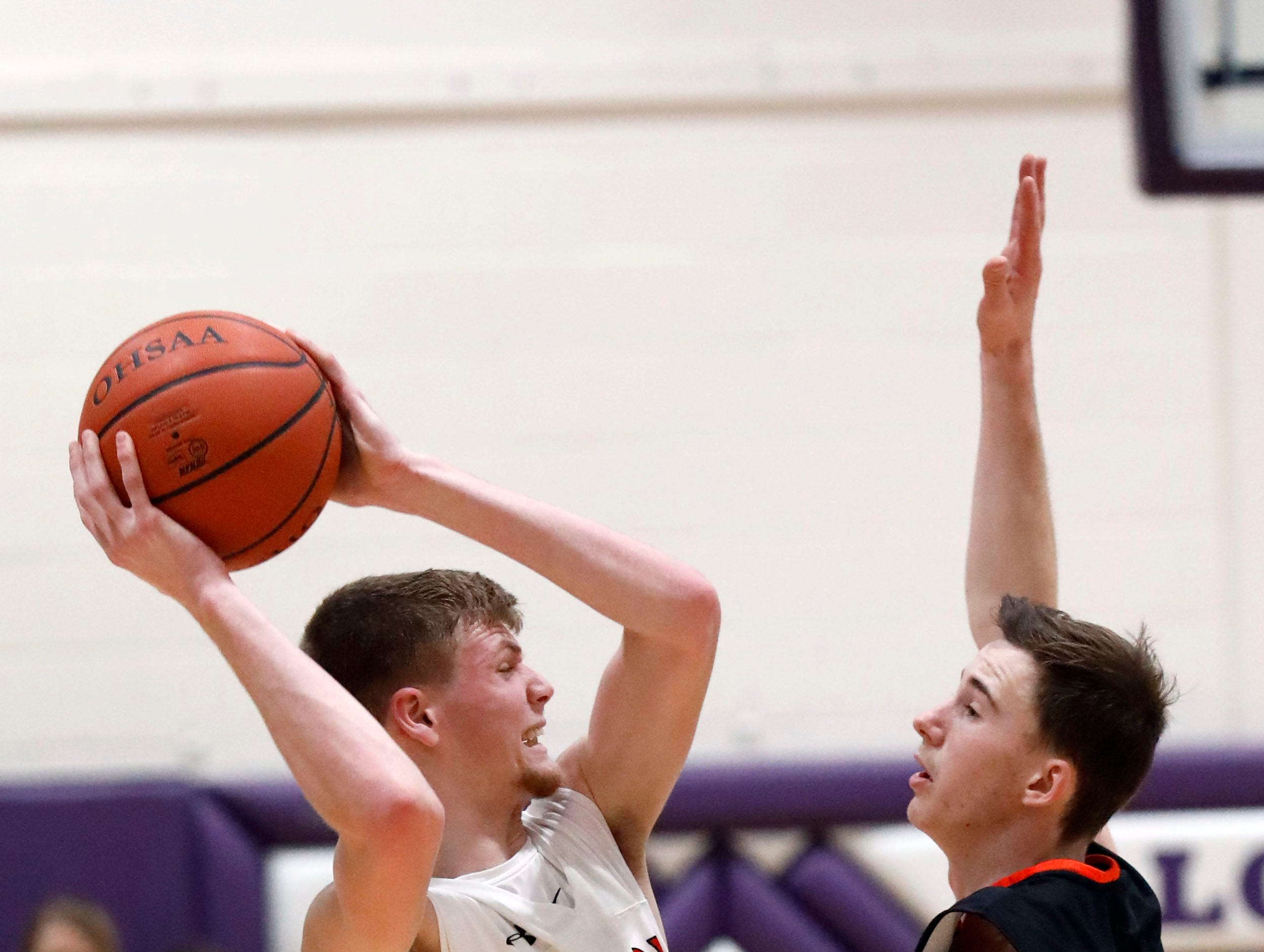 Fairfield Union's Chase Poston looks for an open teammate as he's guarded by Marietta's Mark Duckworth during Saturday's game, Feb. 23, 2019, at Logan High School in Logan. The Falcons defeated Marietta 48-33.