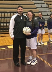 Fowlerville's Jackie Jarvis received a commemorative basketball from coach Billy Selvia after scoring her 1,000th point on Friday, Feb. 22, 2019.
