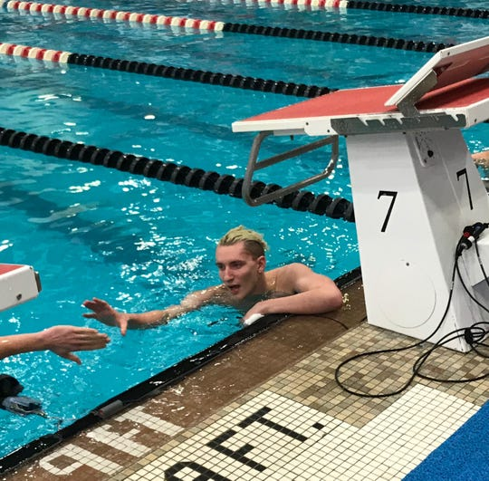 Ontario's Kenton Cordrey reaches out to shake hands with a competitor after swimming in the B finals of the 200 freestyle at the state meet.