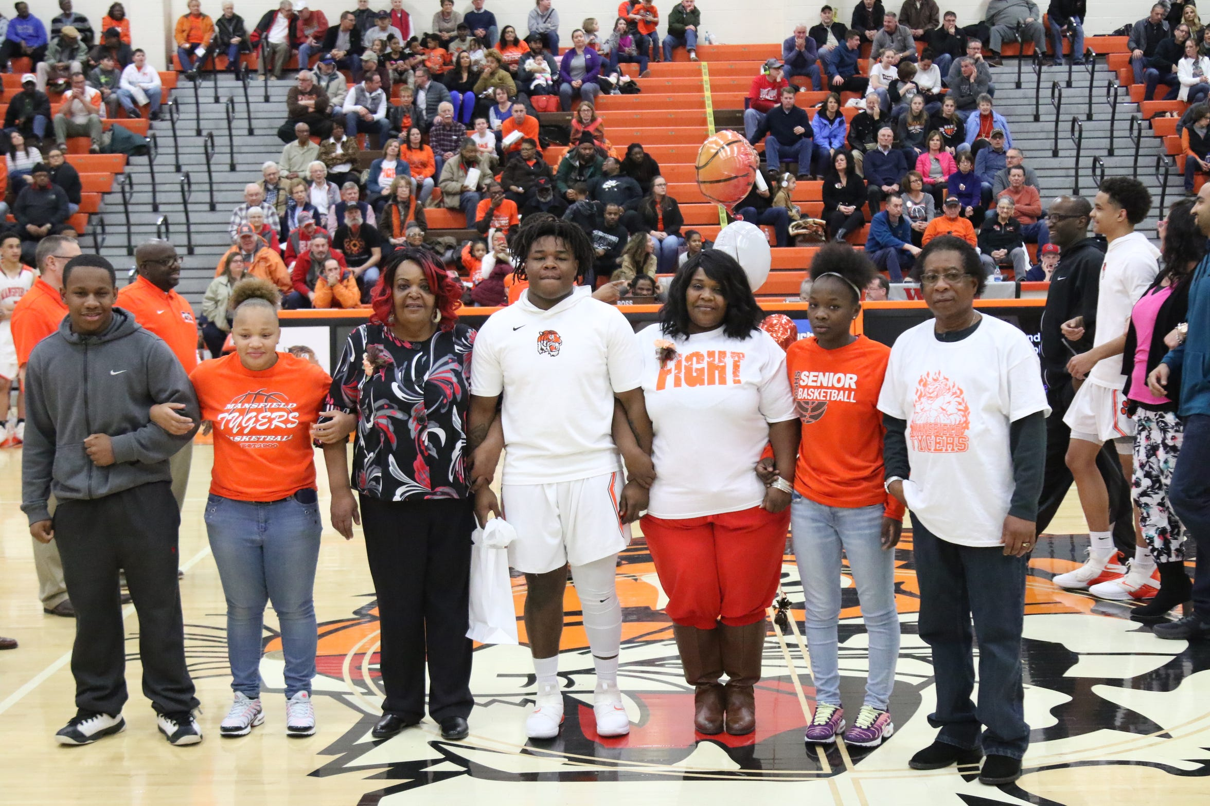 Mansfield Senior's Quan Hilory (center) stands with his family during senior night earlier this season.
