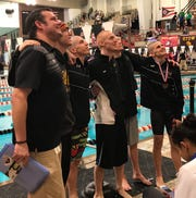 Lexington coach Brock Spurling, along with swimmers Justice Holmes, Wilson Cannon, Connor Miller, Cayman Eichler and Jamin Howe pose for fans taking pictures from high in the stands after the Minutemen make program history by finishing third in the Division II boys standings at the state meet.