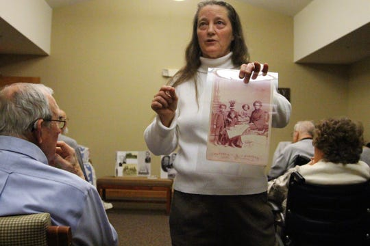 Rebecca McKinney, with the Marion County Historical Society, holds an old  picture of a black family during a presentation about Marion's involvement with the Underground Railroad, a network of secret routes and safe houses established in the United States during the early to mid-19th century.