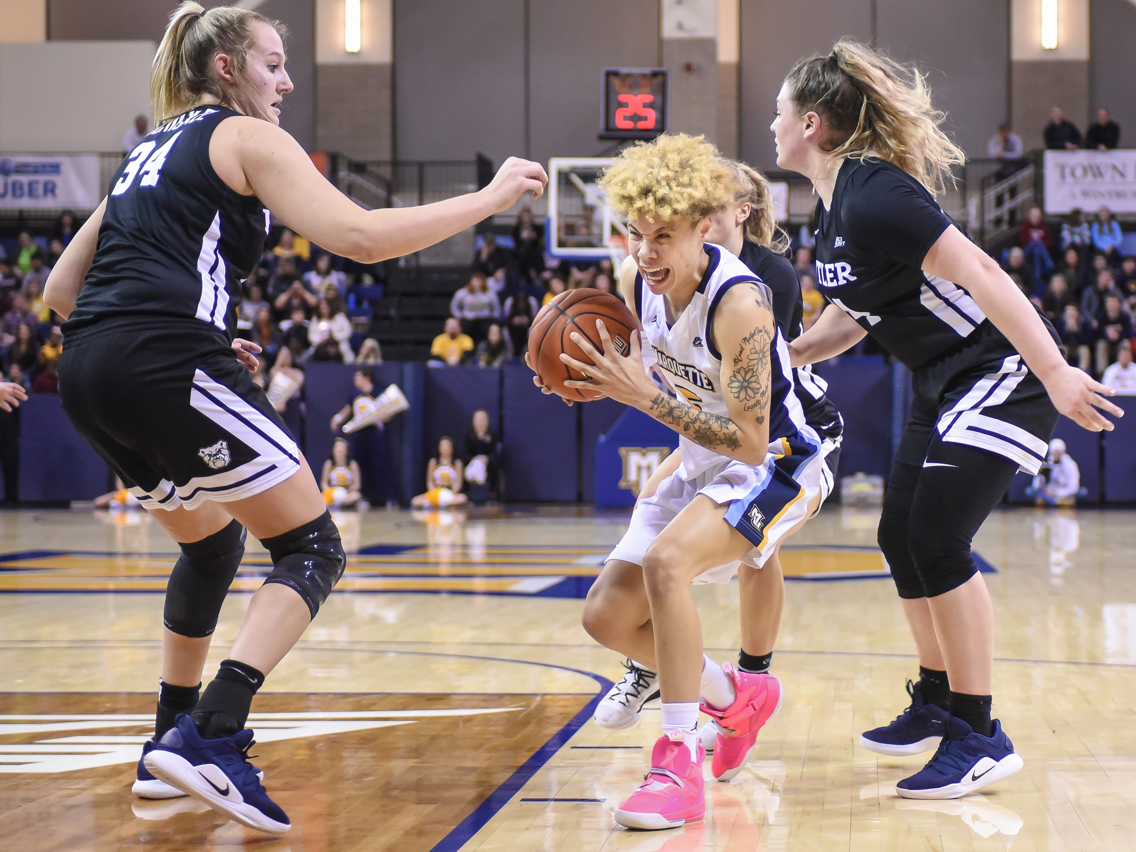 Marquette guard Natisha Hiedeman changes direction while driving between Butler forward/center Tori Schickel (left) and guard Kristen Spolyar in a Big East women's college basketball game Friday, February 22, 2019, at the Al McGuire Center.