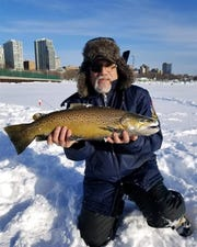 Patrick Caraulia, a U.S. military veteran, holds a brown trout caught in the Milwaukee harbor Feb. 18 during an outing organized by Wisconsin Hero Outdoors.