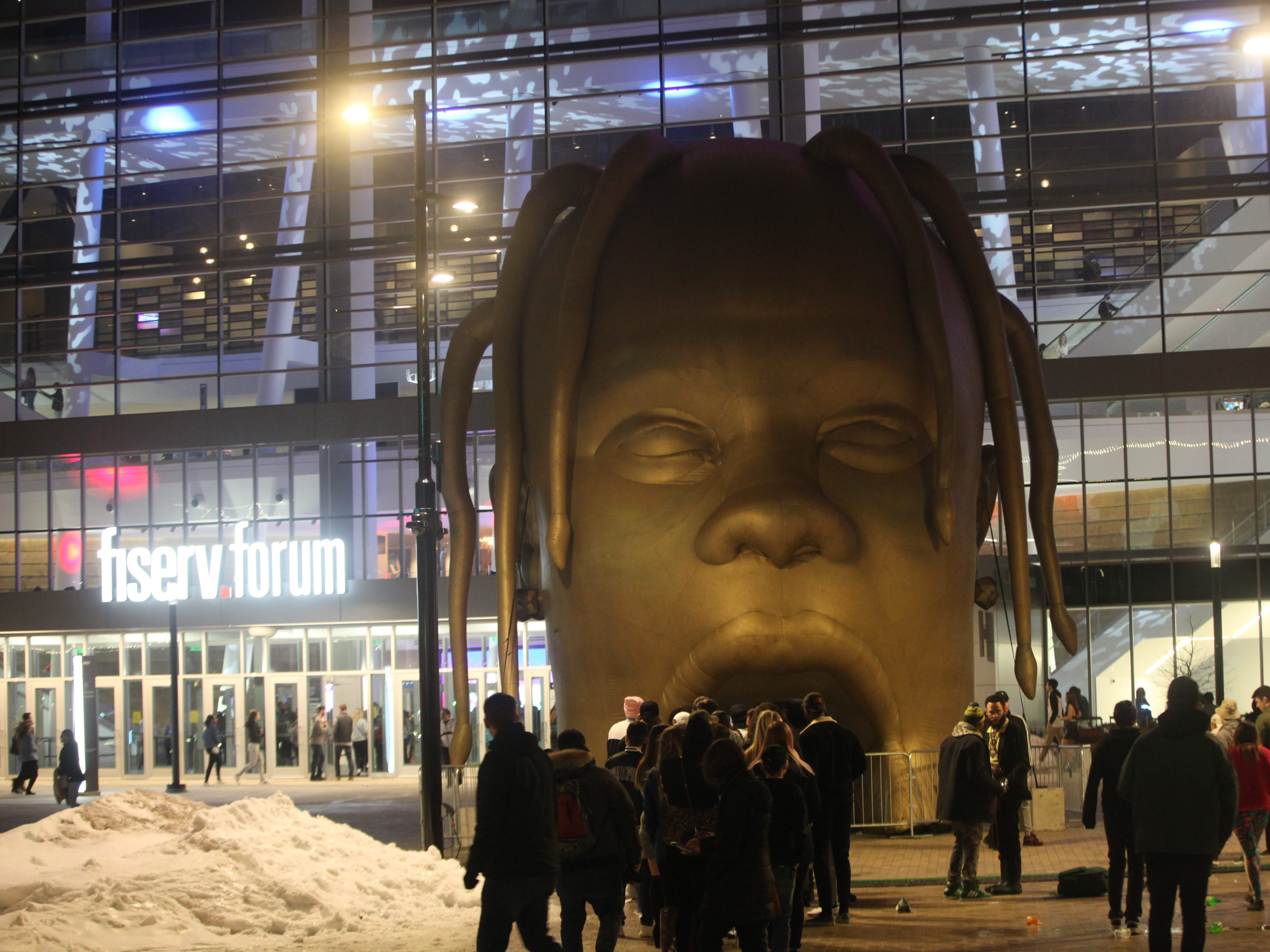 "Fans lined up to take pictures in front of an inflatable Travis Scott head, as seen in the album art for his latest album ""Astroworld,"" before the rapper's show at Fiserv Forum on Feb. 22, 2019."