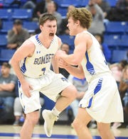 Mountain Home's Hunter Beshears and Talyn Benton celebrate a basket against West Memphis.