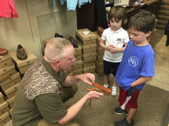 Pete Daugherty, left, shows Claiborne Hincy, 5, and Waler Woods, 7, how to use a box call.