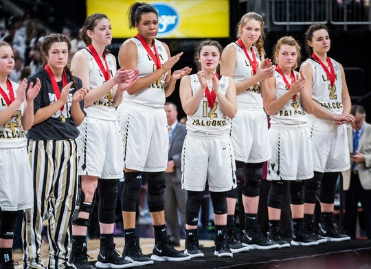Winchester players stand on the podium with their runner-up medals after falling to Oak Hill in the state championship game at Bankers Life Fieldhouse.