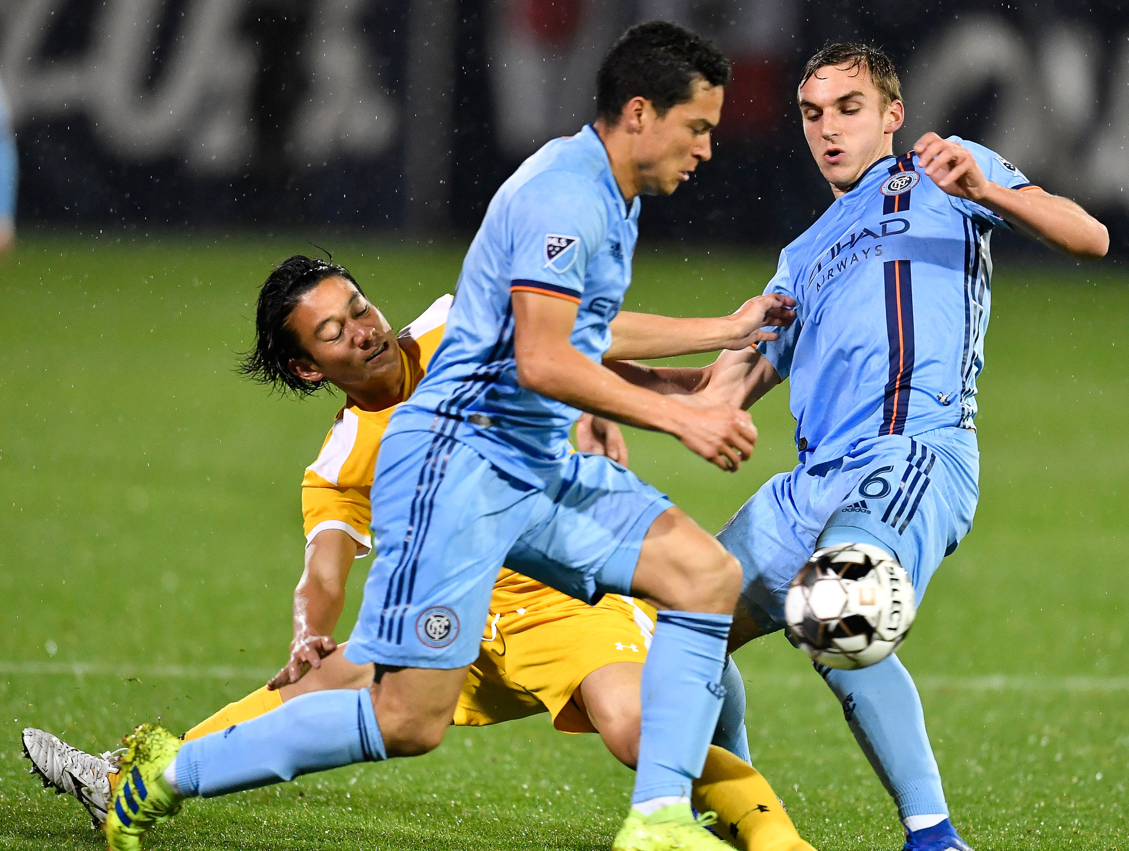 Nashville SC Genki Miyachi gets tripped up by New York City FC midfielder James Sands (16) as midfielder Thomas McNamara (15) races up the field during the second half at First Tennessee Park Friday, Feb. 22, 2019 in Nashville, Tenn.