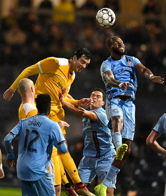 New York City FC defender Sebastien Ibeagha (33) heads the ball away from Nashville SC forward Tucker Hume (12) during the second half at First Tennessee Park Friday, Feb. 22, 2019 in Nashville, Tenn.