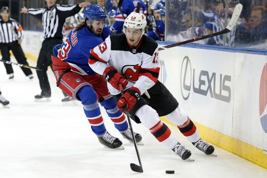 New Jersey Devils center Nico Hischier (13) plays the puck against New York Rangers center Mika Zibanejad (93) during the first period at Madison Square Garden.