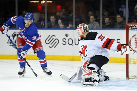 New Jersey Devils goalie Cory Schneider (35) makes a save in front of New York Rangers left wing Chris Kreider (20) during the second period at Madison Square Garden.