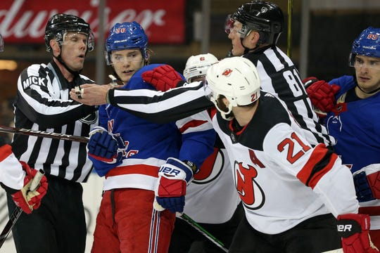 New York Rangers center Lias Andersson (50) is separated from New Jersey Devils right wing Kyle Palmieri (21) by officials during the second period at Madison Square Garden.