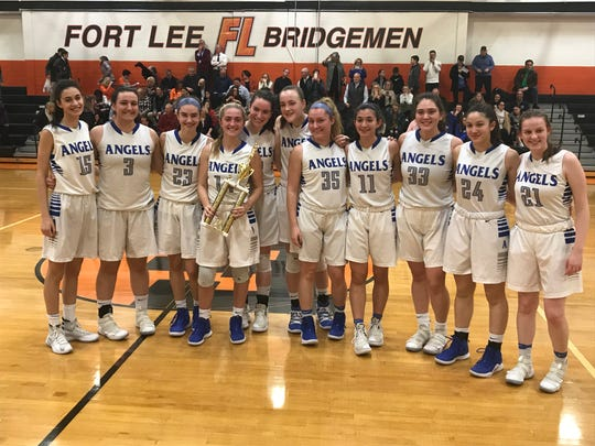 Holy Angels players celebrate with the championship trophy after winning the inaugural Bergen County girls basketball invitational tournament on Friday, Feb. 22, 2019 at Fort Lee. The Angels defeated Pascack Hills, 50-21.