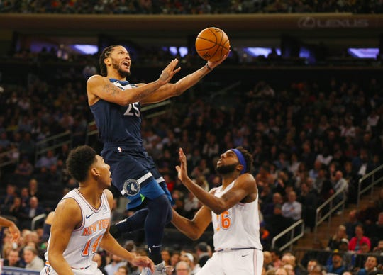 Feb 22, 2019; New York, NY, USA; Minnesota Timberwolves guard Derrick Rose (25) goes up for a shot against New York Knicks guard Allonzo Trier (14) and center Mitchell Robinson (26) during the first half at Madison Square Garden.