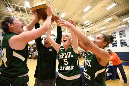 DePaul seniors Vanessa Lomakin (24), Sam Buttitta (5) and Deziah Gonzalez (3) and coach Dave Andre celebrate with the trophy after helping DePaul capture the Passaic County girls basketball championship, 61-46, over Wayne Valley on Saturday, Feb. 23, 2019.