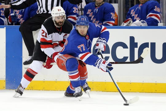 Feb 23, 2019; New York, NY, USA; New York Rangers defenseman Tony DeAngelo (77) plays the puck against New Jersey Devils right wing Kyle Palmieri (21) during the third period at Madison Square Garden.