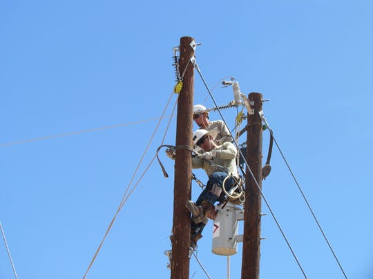 Electrical lineworkers service electrical and telephone poles in Doña Ana County