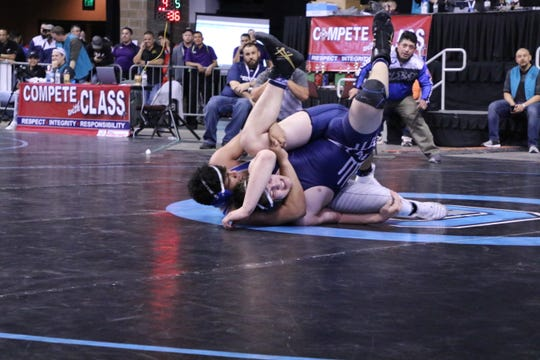 Carlsbad's Jared Duenez goes for a pin against Piedra Vista's Jacob Bartley in the 220-pound division.