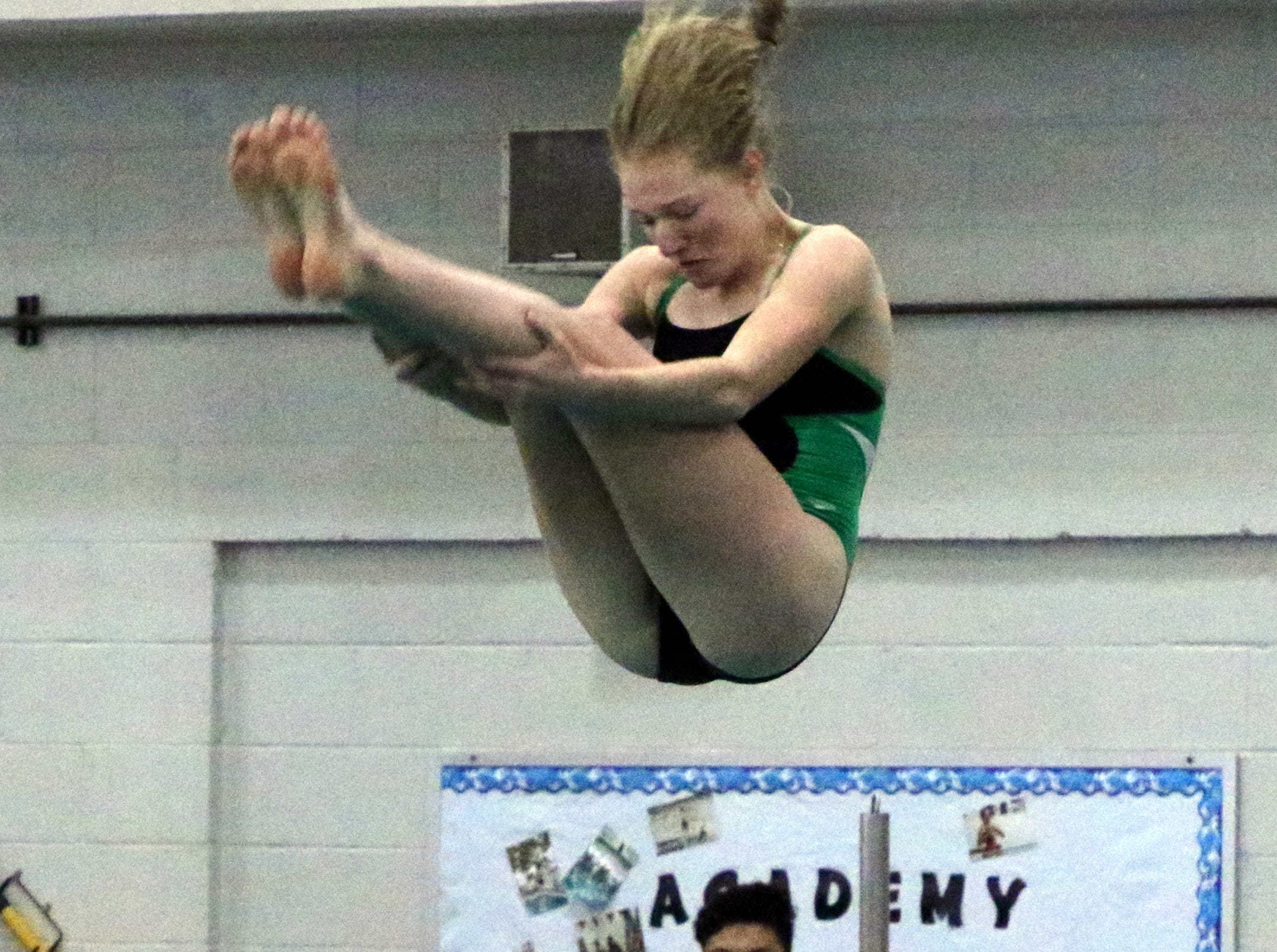 Farmington's Eliza Merrion tucks her legs during one of her dives on Friday. She finished Friday in 11th place.