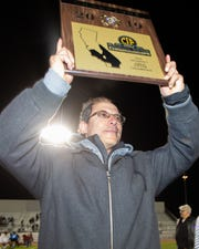 Rams head coach Jorge Chavez holds up the CIF-SS Division 7 championship trophy following Desert Mirage's 1-0 victory over Notre Dame. The championship is Chavez's fourth, and his first with the Desert Mirage girls.