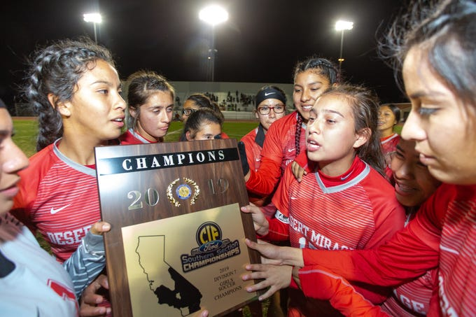 The Desert Mirage varsity soccer team check out their  trophy after winning its first girls' soccer CIF title 1-0 against Notre Dame in overtime.